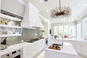 White cabinets with modern glass tile and lighting make for a personalized transitional kitchen design. Photo provided by The Kitchen Source.