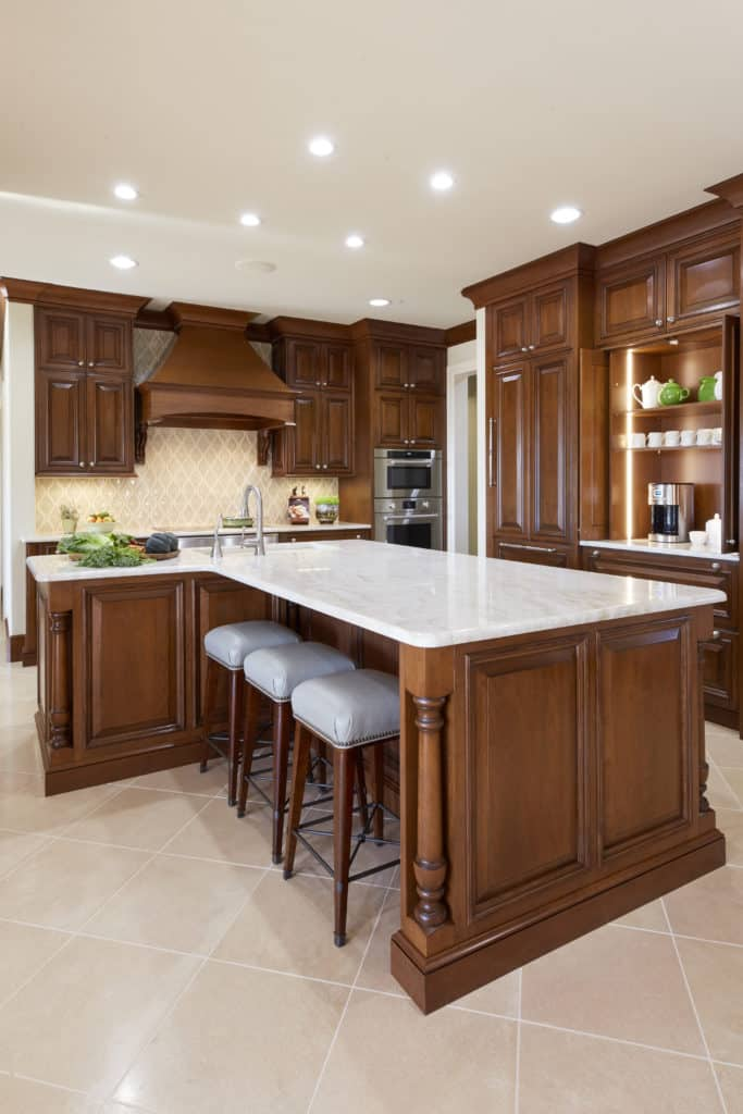 Traditional kitchens have details such as turned columns, stained cabinets, decorative vent hood covers, and raised panel cabinet doors. Photo provided by The Kitchen Source.