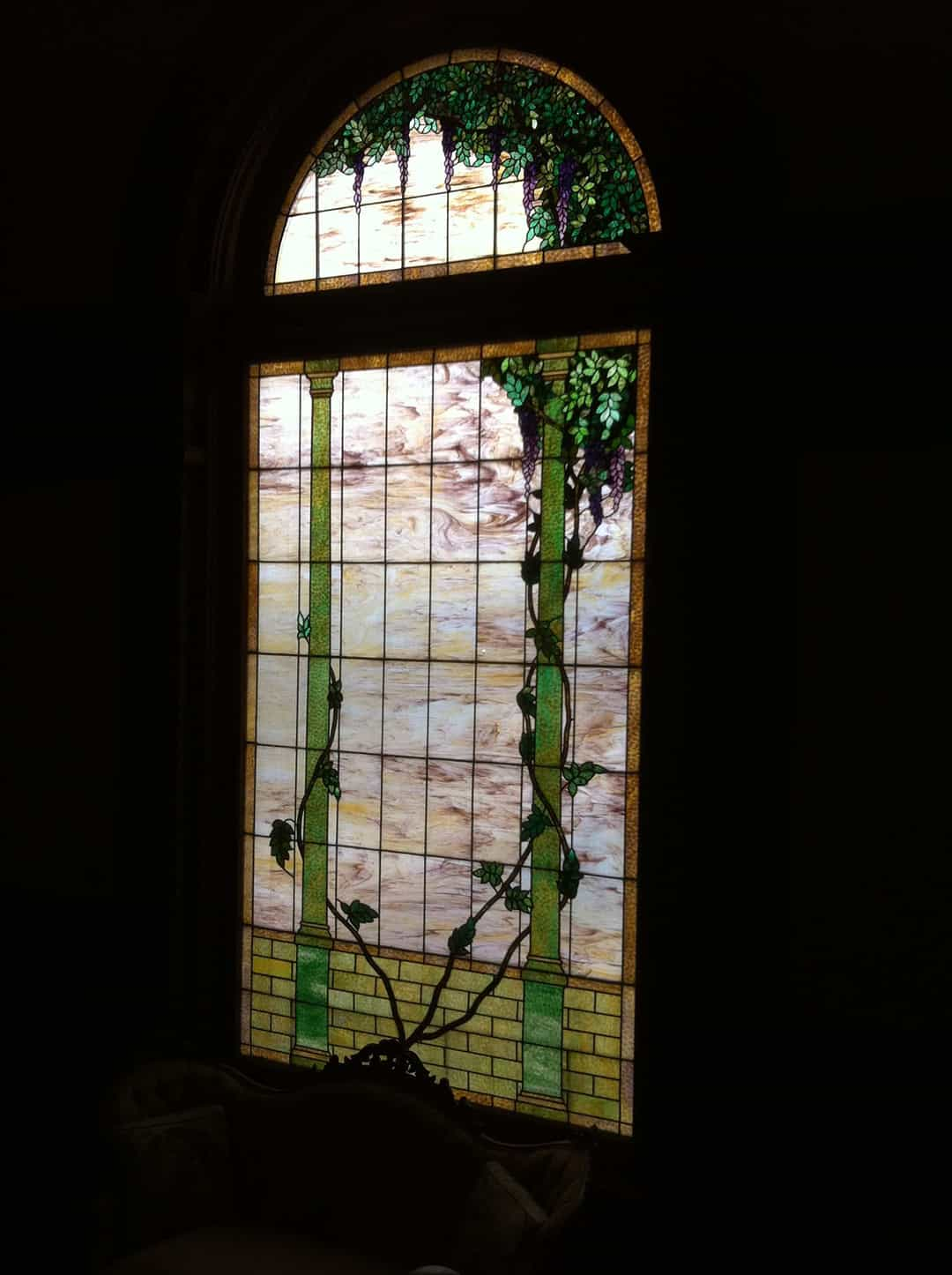 Tiffany inspired stained glass window stands over ten feet tall at the landing of the grand stair