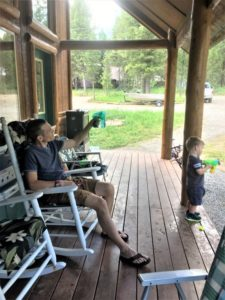Dad and son enjoy time on porch at log cabin