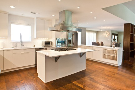 HPD Architecture White Kitchen with Cooktop Island and Access to Dining Room